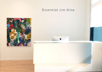 Image of front desk in gallery with abstract Jim Dine painting in the background